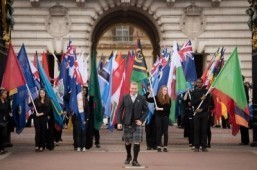 Former British cyclist Sir Chris Hoy (C) leads a procession of Commonwealth flags during the launch of the 2014 Glasgow Commonwealth Games baton relay at Buckingham Palace in London, on October 9, 2013. ©AFP PHOTO/Leon Neal
