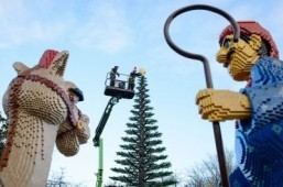 Legoland model maker Katrina James (R) placing a Lego star onto the top of a 8m tall Lego Christmas tree during a photocall at Legoland Windsor Resort, west of London ©AFP PHOTO / LEON NEAL