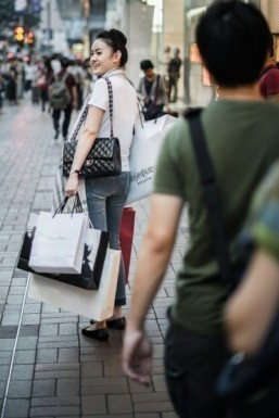 A woman carries luxury shopping bags in Hong Kong. Tourists from mainland China enjoy added cachet from foreign-bought items. © AFP PHOTO / Philippe Lopez