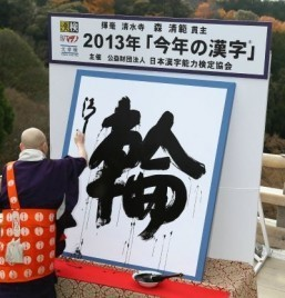 "Seihan Mori, the chief priest of Kyoto's famous Kiyomizu temple, displays his caligraphy of a kanji (or Chinese character), ""wa"" meaning ""ring"", which was selected as the single best kanji to symbolize the year 2013 at the temple in Kyoto, western Japan on December 12, 2013. ©AFP PHOTO / JIJI PRESS"