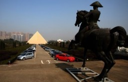This picture taken on December 31, 2013, shows a 130-foot high pyramid (L) built by Chinese multi-millionaire Zhang Yue, on his corporate campus in Changsha, China's Hunan province. A Chinese multi-millionaire who built himself an Egyptian pyramid and a replica of Versailles vows to construct the world's tallest building in just six months -- despite authorities preventing work amid safety concerns. ©AFP PHOTO