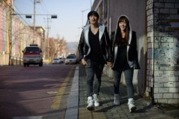 In a photo taken on February 11, 2014 couple Baek Eun-Joo (R) and Lee Sang-Jun (L) who run 'Ggumddakji', an online shopping mall specialising in couples clothing, walk near their office in Seoul. ©AFP PHOTO / Ed Jones