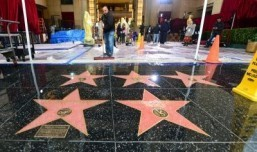 Water from heavy rain is swept off the floor in front of the Dolby Theatre in Hollywood amid ongoing preparations on March 1, 2014 for the 86th Academy Awards on March 2nd, 2014 in Hollywood, California. ©AFP PHOTO FREDERIC J. BROWN
