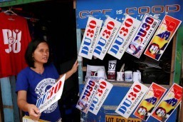 A woman sells souvenir car plates with images and slogans of presumptive president Rodrigo Duterte along a sidewalk in Davao City on Wednesday. Davaoeños are ecstatic with the results of the general elections, with their mayor expected to set a historical first for Mindanao. (MNS photo)