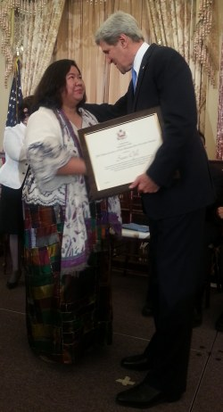 "US Secretary of State John Kerry hands over the ""2013 Hero Acting To End Modern-Day Slavery Award"" to OFW advocate Susan Ople"
