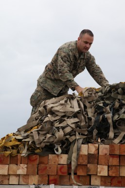 A U.S. Marine uses cargo nets to secure a load of palletized equipment on a KC-130J Hercules aircraft at Marine Corps Air Station Futenma, Okinawa, Japan, during preparation for a humanitarian assistance and disaster relief mission to the Philippines in the wake of Typhoon Haiyan, Nov. 11, 2013. The Marines are assigned to the 3rd Expeditionary Force. U.S. Marine Corps photo by Lance Cpl. David N. Hersey