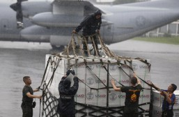 US carrier arrives with aid mass burial begins