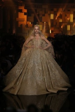Elie Saab - Haute Couture - fall/winter 2015-2016 Gold sleeveless gown fully embroidered with large floral leaf appliques with silk thread and sequins, a voluminous full skirt and long train, paired with a long embroidered veil ©Elie Saab