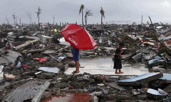 Residents stand on the ruins of their house amidst other destroyed houses after Super Typhoon Haiyan battered Tacloban city in central Philippines November 10, 2013. One of the most powerful storms ever recorded killed at least 10,000 people in the central Philippines province of Leyte, a senior police official said on Sunday, with coastal towns and the regional capital devastated by huge waves. Super typhoon Haiyan destroyed about 70 to 80 percent of the area in its path as it tore through the province on Friday, said chief superintendent Elmer Soria, a regional police director. (MNS photo)